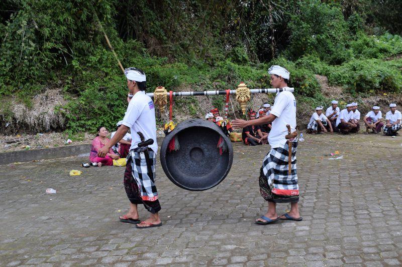 Balinese men carrying traditional gong