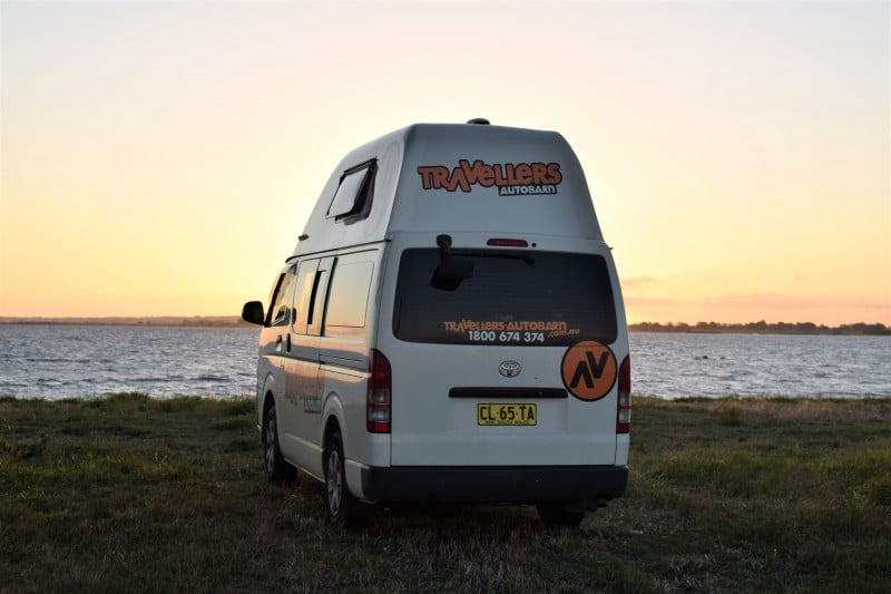 Campervan at a lake by sunset