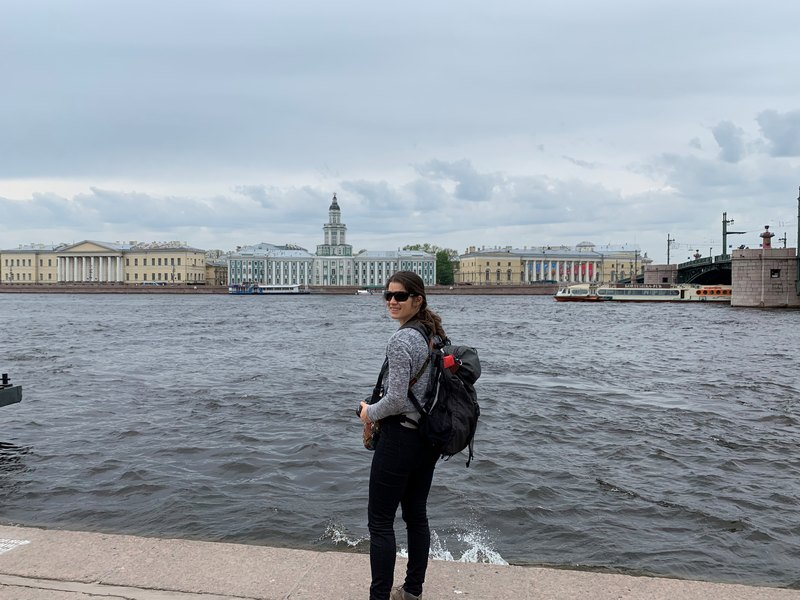 Woman standing in front of Neva River with Kunstkamera in the background - St. Petersburg Russia