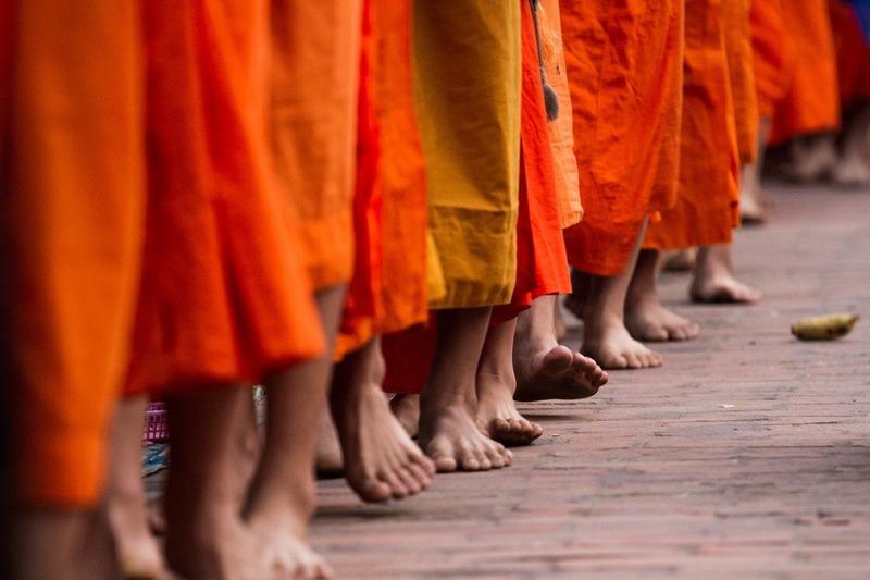 Feet of monks in orange robes in Luang Prabang